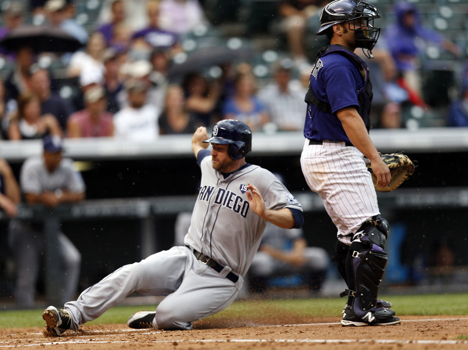 Photo - San Diego Padres' Chase Headley scores on a Brooks Conrad sacrifice fly as Colorado Rockies catcher Michael McKenry wartches the field during the fourth inning of an MLB baseball game on Monday, July 7, 2014, in Denver (AP Photo/Jack Dempsey)