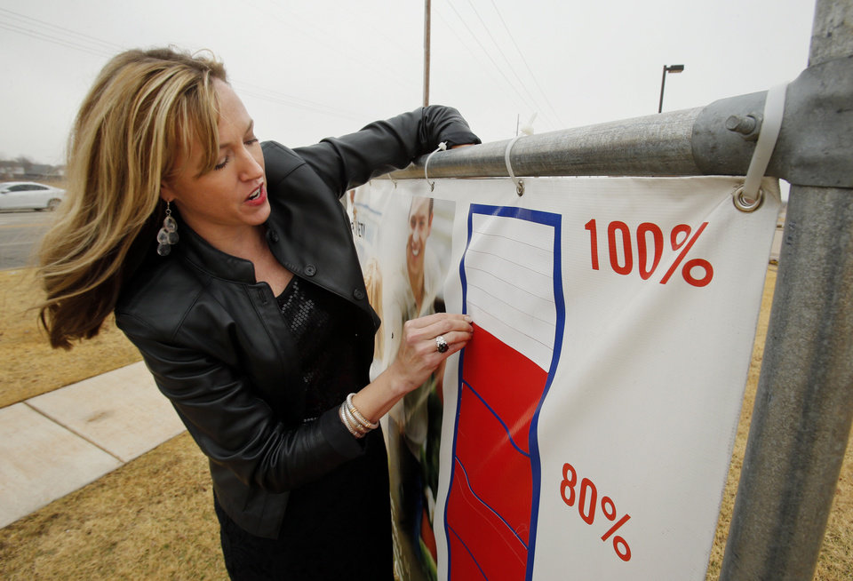 United Way of Norman President Kristin Collins updates a street sign to indicate the agency�s fundraising success. PHOTO BY STEVE SISNEY, THE OKLAHOMAN