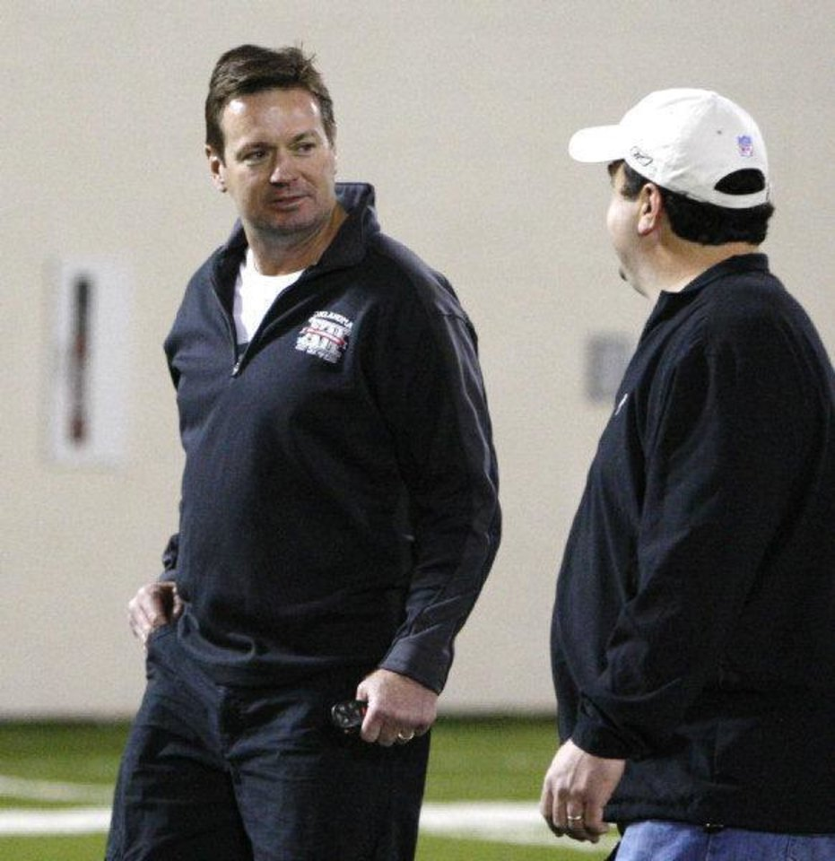 Photo - Oklahoma head coach Bob Stoops, left, talks with Paul Guenther, left, of the Cincinnati Bengals at Oklahoma's Pro Day footbal workout in Norman, Okla., Tuesday, March 8, 2011. (AP Photo/Sue Ogrocki)  Sue Ogrocki