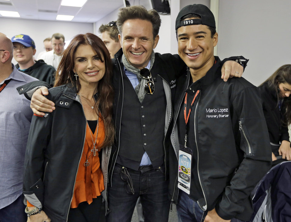 Roma Downey, left, poses with Mark Burnett, center, and Mario Lopez prior to the start of the STP 500 Sprint Cup  series auto race at Martinsville Speedway in Martinsville, Va., Sunday, April 7, 2013.  (AP Photo/Steve Helber)