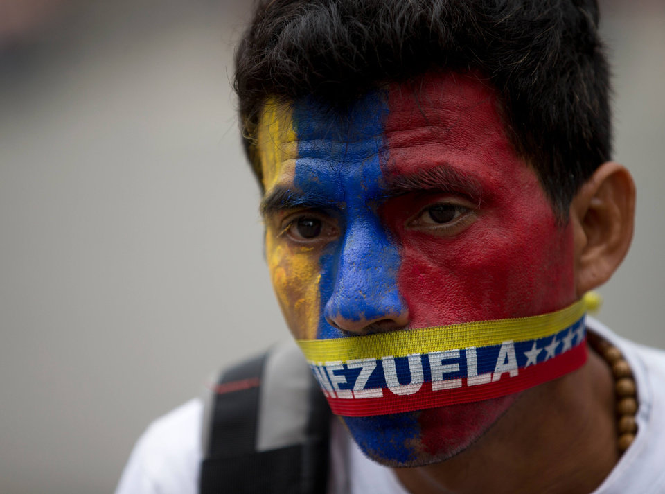 Photo - A man wears a narrow strip in the colors of Venezuela's flag over his mouth in protest of officials breaking up camps maintained by student protesters, in Caracas, Venezuela, Thursday, May 8, 2014. Hundreds of security forces broke up four camps maintained by student protesters, arresting more than 200 people in a pre-dawn raid. The camps of small tents were installed more than a month ago in front of the UN building and other anti-government strongholds in the capital to protest against President Nicolas Maduro's government. (AP Photo/Fernando Llano)
