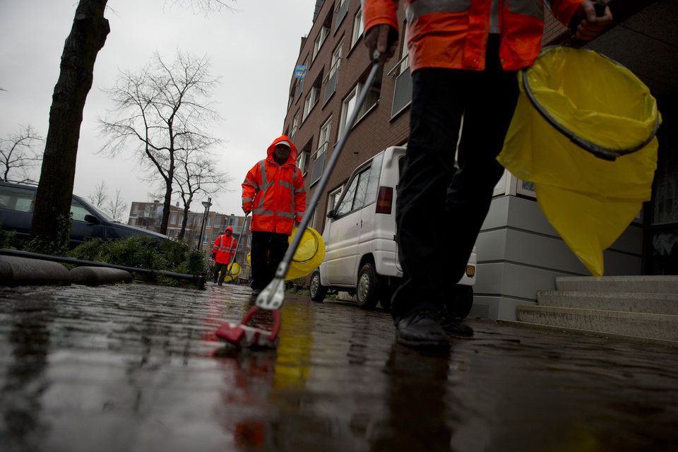 Photo - Three alcoholics set out on their daily route to collect litter in Amsterdam's eastern part Wednesday Jan. 15, 2014. In a pilot project that has drawn attention in the Netherlands and around the world, the city has teamed up with a charity organization in hopes of improving the neighborhood and possibly improving life for the alcoholics. Not by trying to cure them, but instead by offering to fund their drinking outright. That is, participants are given beer in exchange for a little work collecting litter, eating a decent meal, and sticking to their schedule. (AP Photo/Peter Dejong)