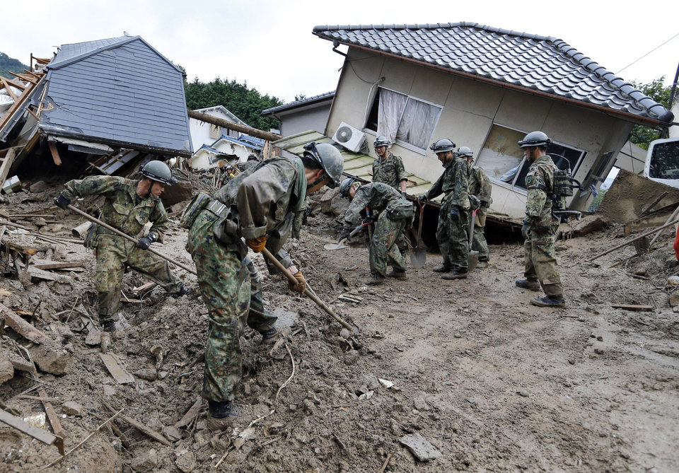Photo - Japan Ground Self Defense Force personnel search for missing residents in a mud-ridden residential area following a massive landslide in Hiroshima, western Japan, Thursday, Aug. 21, 2014. Rain-sodden slopes collapsed in torrents of mud, rock and debris Wednesday on the outskirts of Hiroshima city, killing more than 30 people and leaving a several missing, Japanese police said. (AP Photo/Kyodo News) JAPAN OUT