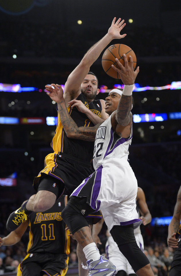 Photo - Sacramento Kings guard Isaiah Thomas, right, puts up a shot as Los Angeles Lakers guard Jordan Farmar defends during the second half of an NBA basketball game, Friday, Feb. 28, 2014, in Los Angeles. (AP Photo/Mark J. Terrill)