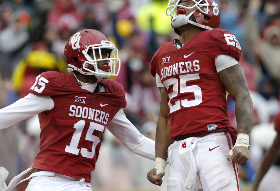 Photo - Oklahoma's Joe Mixon (25) and Jeffery Mead (15) celebrate a Mixon touchdown in the fourth quarter during the Bedlam college football game between the Oklahoma Sooners (OU) and the Oklahoma State Cowboys (OSU) at Gaylord Family - Oklahoma Memorial Stadium in Norman, Okla., Saturday, Dec. 3, 2016. OU won 38-20. Photo by Sarah Phipps, The Oklahoman