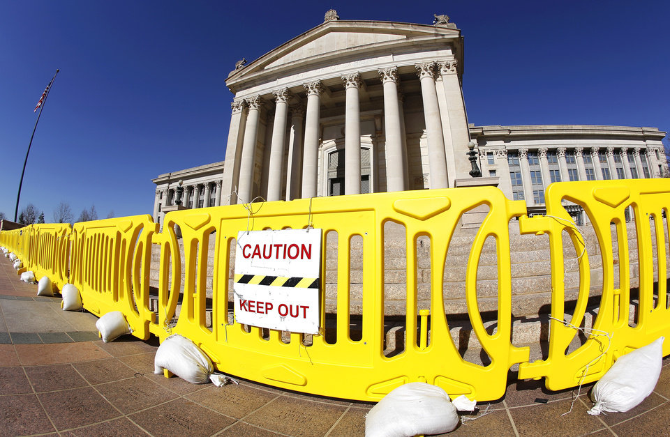Bright yellow barriers prevent pedestrians from encroaching into the south plaza area where debris occasionally falls from crumbling sections of the state Capitol on Thursday, Jan. 31, 2013. Photo by Jim Beckel, The Oklahoman