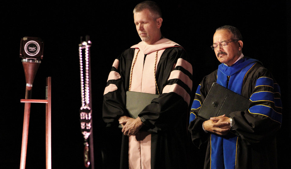 Photo - Dr. John Fletcher, Professor of Music, left, and Dr. Alan Martin,  Dean of Biblical Studies bow their heads in prayer during the inauguration of John deSteiguer as the new President of Oklahoma Christian University in Oklahoma City , Monday August 27, 2012. Photo By Steve Gooch, The Oklahoman