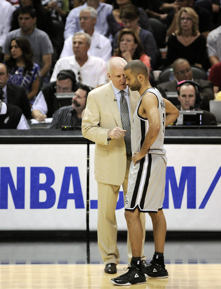 Photo - San Antonio Spurs head coach Gregg Popovich, left, talks with Spurs' Tony Parker, of France, during the second half of Game 1 of the Western Conference final NBA basketball playoff series against the Memphis Grizzlies, Sunday, May 19, 2013, in San Antonio. San Antonio won 105-83. (AP Photo/Darren Abate)