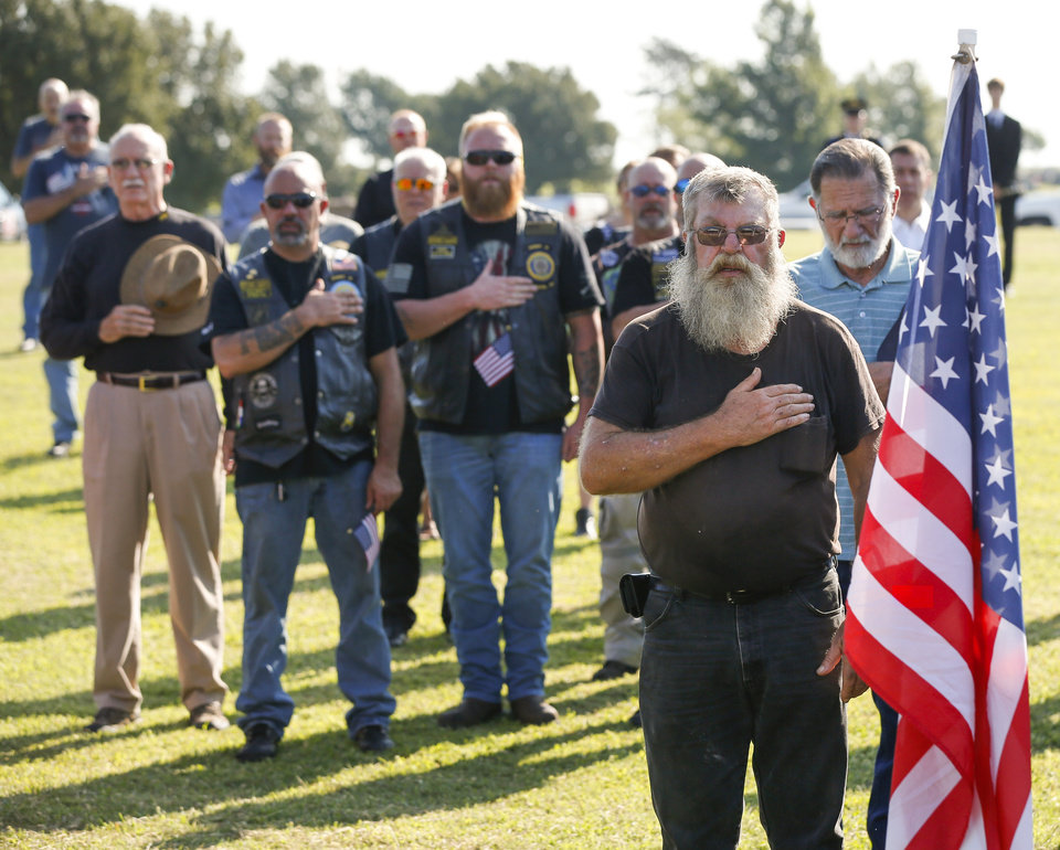 Photo - Mourners stand for the Pledge of Allegiance during the funeral service for World War II veteran Herman White at Grace Hill Cemetery in Perry, Okla., Wednesday, Sept. 4, 2019. Hundreds of people attended Navy Seaman 2nd Class White's funeral after learning that he had no surviving family members to be there. [Nate Billings/The Oklahoman]