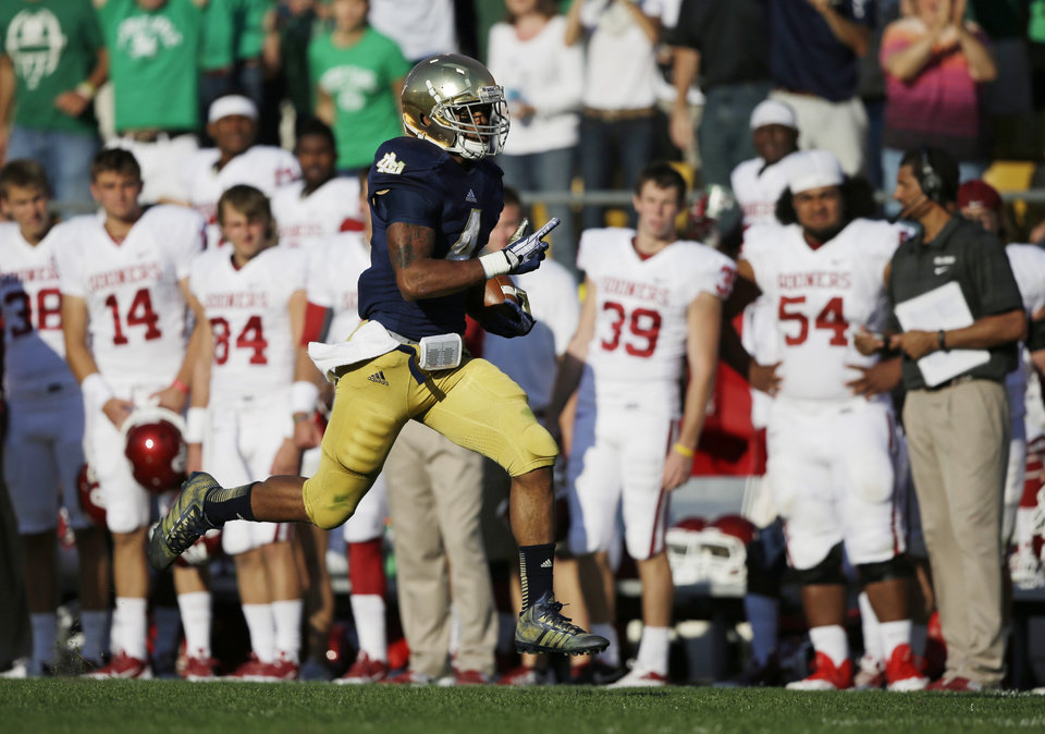 Photo - Notre Dame's George Atkinson III (4) runs 80-yards for a touchdown during the second half of an NCAA college football game against Oklahoma Saturday, Sept. 28, 2013, in South Bend, Ind. Oklahoma defeated Notre Dame 35-21. (AP Photo/Darron Cummings)  ORG XMIT: INDC117