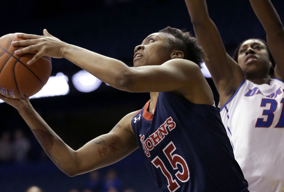 Photo - St. John's guard Danaejah Grant, left, drives to the basket DePaul forward Jasmine Penny during the first half of an NCAA college basketball game in the final of the 2014 Big East women's basketball tournament in Rosemont, Ill., Tuesday, March 11, 2014. (AP Photo/Nam Y. Huh)