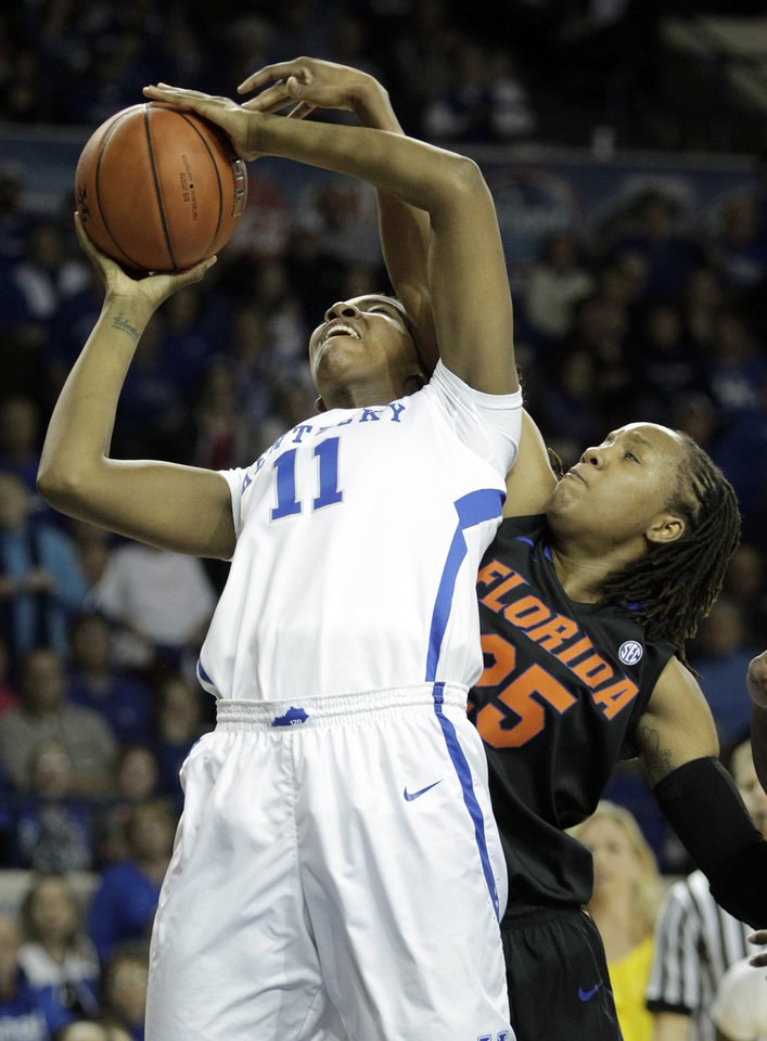 Photo - Kentucky's DeNesha Stallworth (11) shoots under pressure from Florida's Christin Mercer during the first half of an NCAA college basketball game on Sunday, Jan. 5, 2014, in Lexington, Ky. (AP Photo/James Crisp)