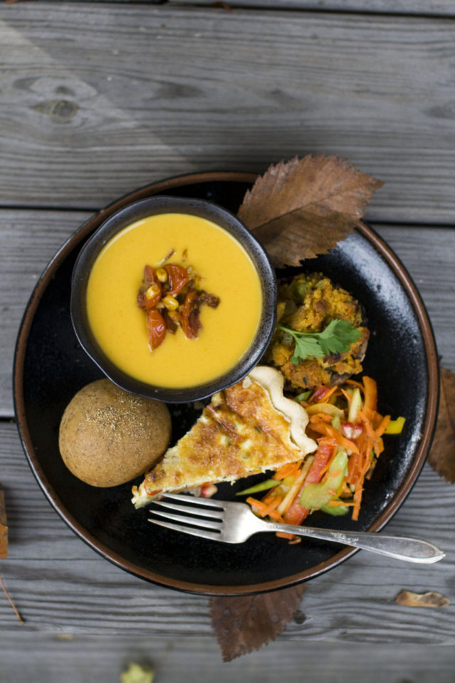 A vegetarian Thanksgiving dinner of red bell pepper and apple slaw, no knead flax rolls, roasted vegetable quiche, corn bread stuffing mushrooms and squash bisque with pan roasted corn salsa is shown served on a table in Concord, N.H. AP PHOTO Matthew Mead - AP