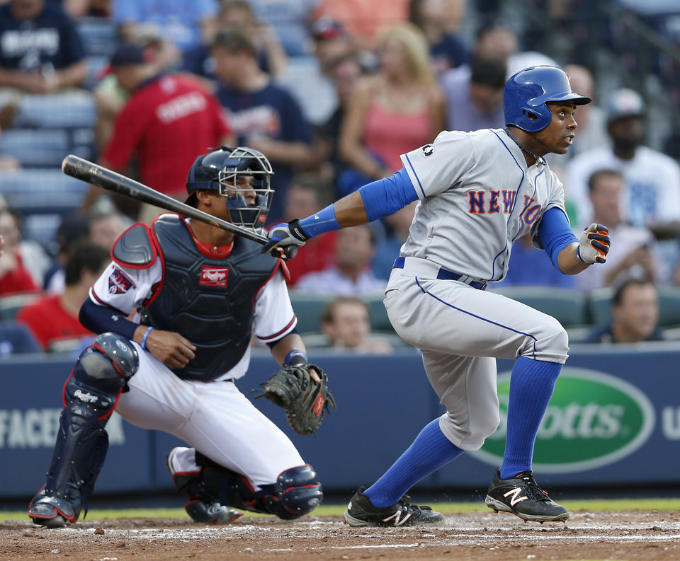 Photo - New York Mets' Curtis Granderson (3) follows through on a two-run home run as Atlanta Braves catcher Christian Bethancourt (25) looks on in the third inning of a baseball game in Atlanta, Tuesday, July 1, 2014.  (AP Photo/John Bazemore)
