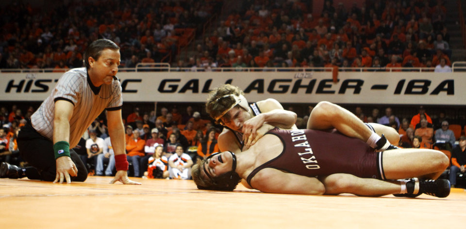 Photo - Oklahoma State 157-pound wrestler Alex Dieringer holds down Oklahoma's Dryden Dennis as Dennis tries to escape in a wrestling dual between Oklahoma State and Oklahoma at Gallagher Iba Arena in Stillwater on Feb. 9, 2014. Photo by KT King/For the Oklahoman