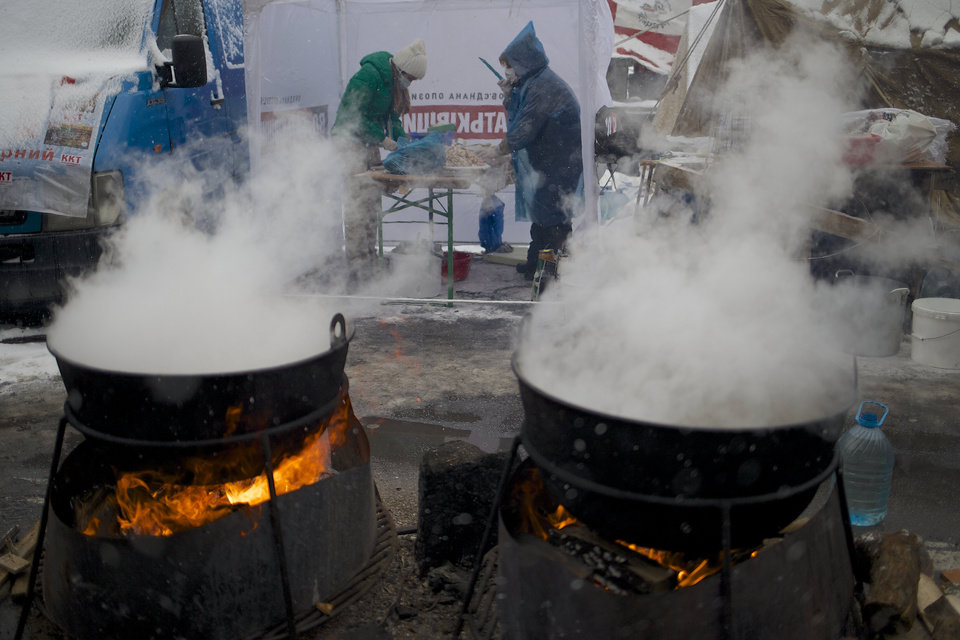Photo - Pro-European Union activists cook meals next to their tent camp on the Independence Square in Kiev, Ukraine, Monday, Dec. 9, 2013. The protesters rose up against President Viktor Yanukovych after he spiked a deal for integration with the European Union and decided to restore trade ties with Russia instead. (AP Photo/Alexander Zemlianichenko)
