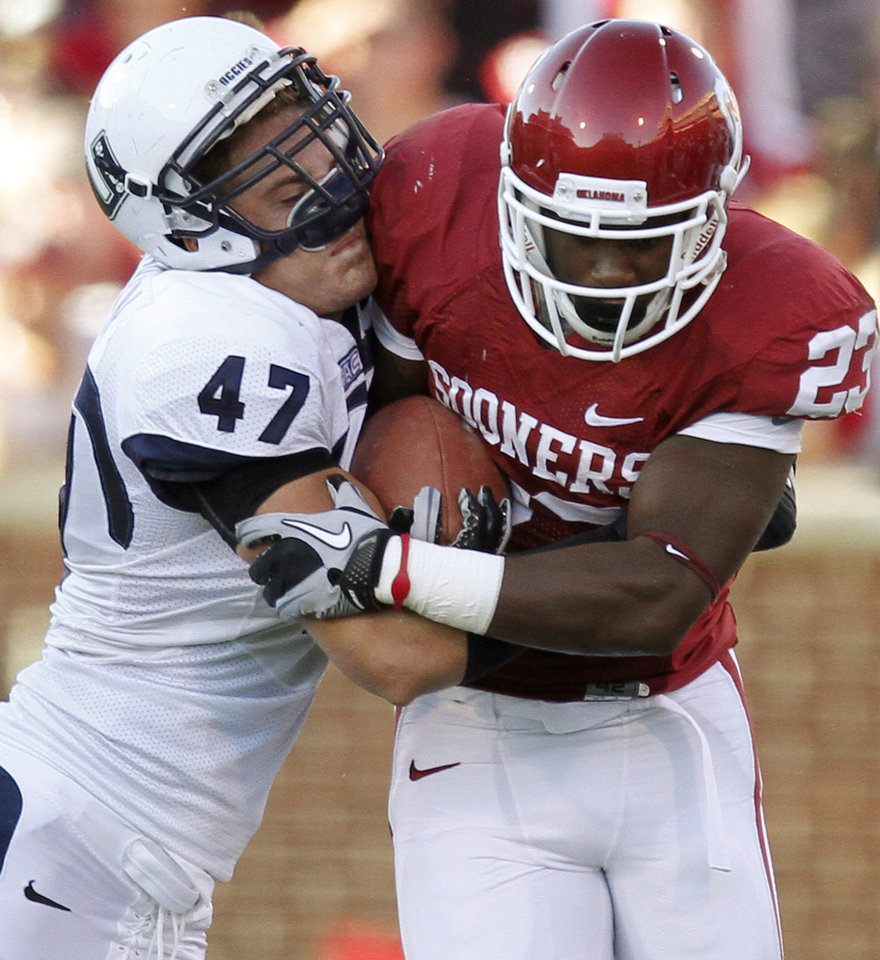 Photo - OU's Jermie Calhoun fights off Utah State's Levi Koskan during the first half of the college football game between the University of Oklahoma Sooners (OU) and Utah State University Aggies (USU) at the Gaylord Family-Oklahoma Memorial Stadium on Saturday, Sept. 4, 2010, in Norman, Okla.   Photo by Bryan Terry, The Oklahoman