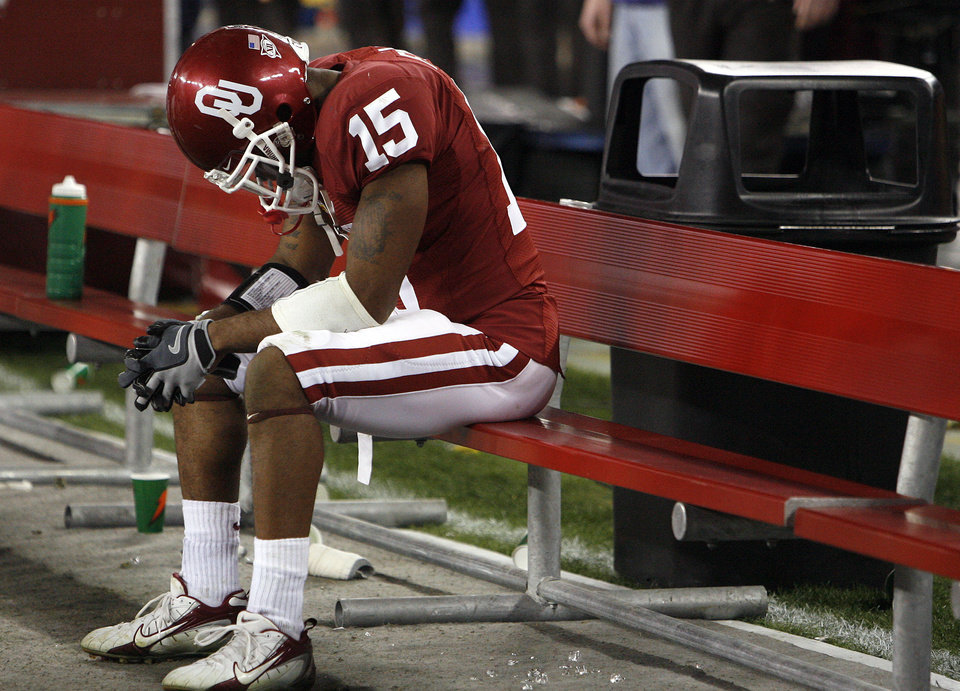 Photo - Oklahoma's Dominique Franks (15) sits on the bench hanging his head after the Sooners 48-28 loss to West Virginia in the Fiesta Bowl college football game between the University of Oklahoma Sooners (OU) and the West Virginia University Mountaineers (WVU) at The University of Phoenix Stadium on Wednesday, Jan. 2, 2008, in Glendale, Ariz. 