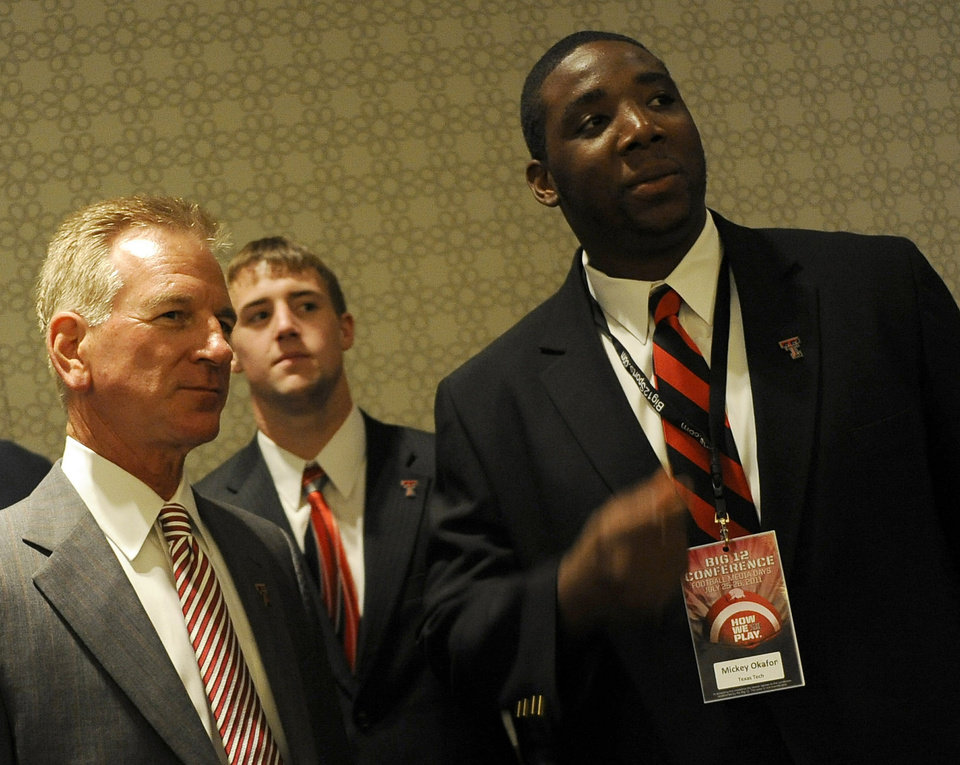 Photo - From left, Texas Tech head coach Tommy Tuberville, safety Cody Davis and offensive lineman Mickey Okafor look on as Oklahoma answers questions during NCAA college football Big 12 Media Days, Tuesday, July 26, 2011, in Dallas. (AP Photo/Matt Strasen)