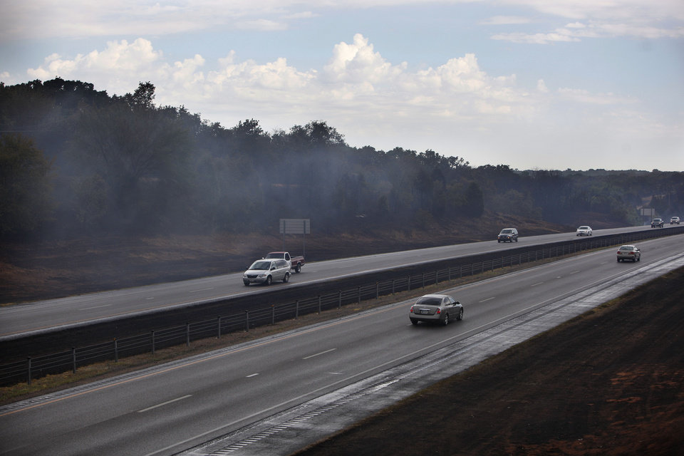 Smoke rises from burned grass on Interstate 35 in Edmond, Okla.,  Sunday, Aug. 7, 2011. Photo by Sarah Phipps, The Oklahoman