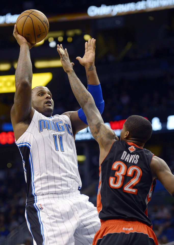 Photo - Orlando Magic forward Glen Davis (11) goes up for a shot in over Toronto Raptors forward Ed Davis during the first half of an NBA basketball game in Orlando, Fla., Thursday, Jan. 24, 2013.(AP Photo/Phelan M. Ebenhack)