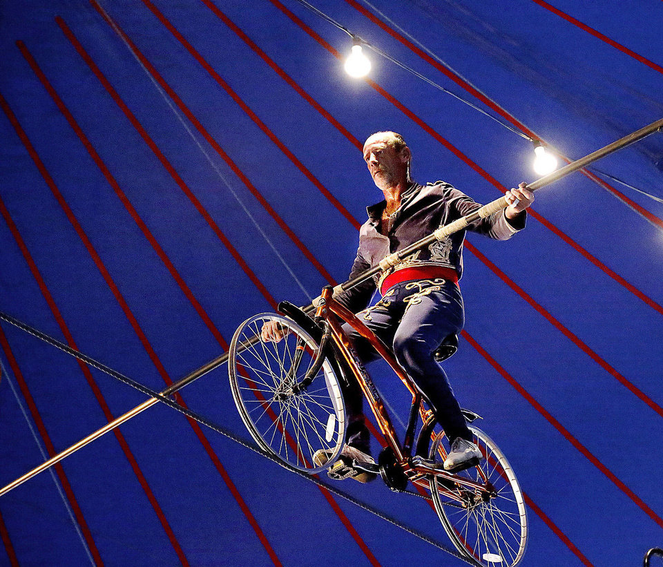 Photo - Circus performer Jim Decker uses a 19- foot pole to balance himself on a bicycle as he rides across a tightrope stretched 20 feet above the ground. Photo  by Jim Beckel, The Oklahoman.  Jim Beckel - THE OKLAHOMAN