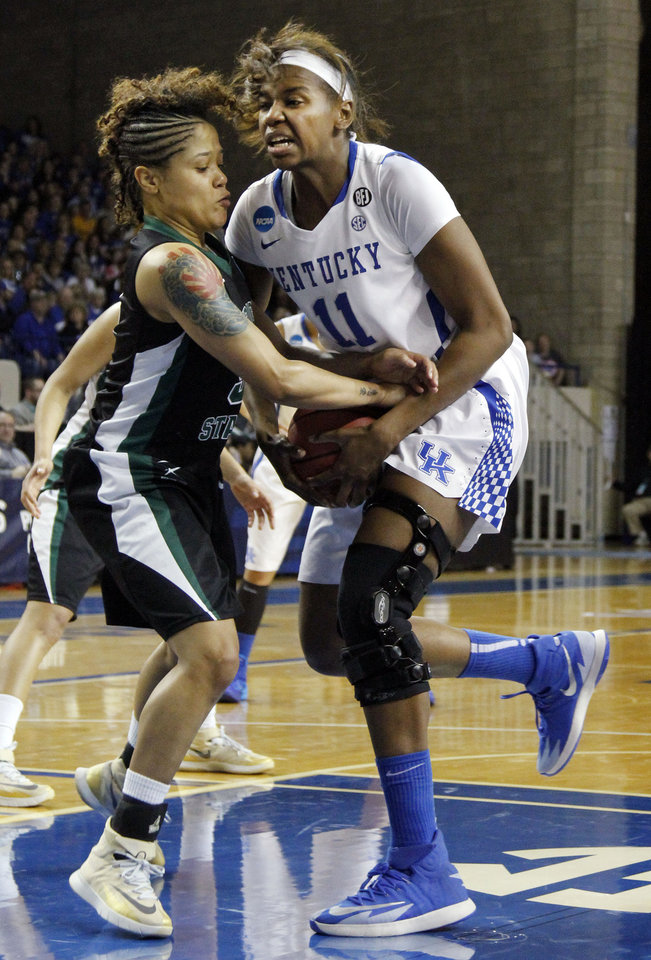 Photo - Wright State's Sarah Hunter, left, and Kentucky's DeNesha Stallworth get tied up during the second half of a first-round game in the NCAA women's college basketball tournament in Lexington, Ky., Saturday, March 22, 2014. Kentucky won 106-60. (AP Photo/James Crisp)