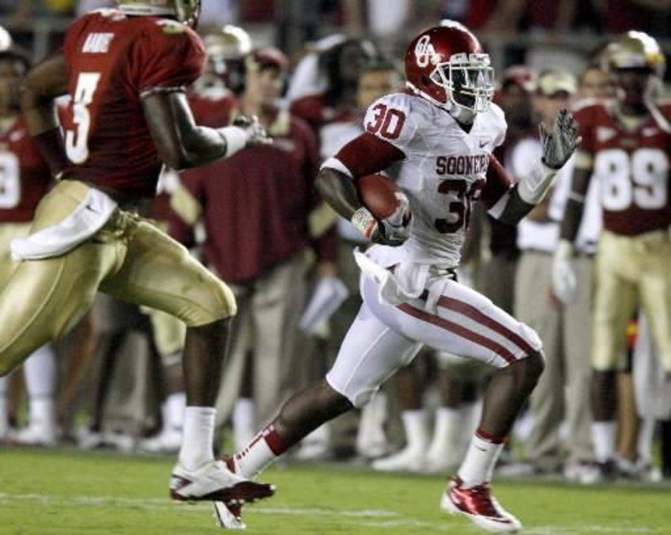 Oklahoma's Javon Harris (30) runs past Florida's EJ Manuel (3) after an interception during a college football game between the University of Oklahoma (OU) and Florida State (FSU) at Doak Campbell Stadium in Tallahassee, Fla., Saturday, Sept. 17, 2011. Photo by Bryan Terry, The Oklahoman.