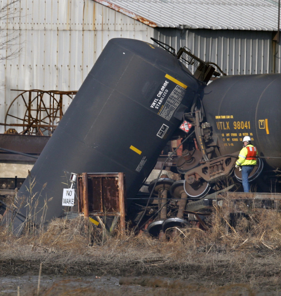 Photo - An official stands by derailed freight train tank cars in Paulsboro, N.J., Friday, Nov. 30, 2012. People in three southern New Jersey towns were told Friday to stay inside after a freight train derailed and several tanker cars carrying hazardous materials toppled from a bridge and into a creek. At least one tanker car may contain vinyl chloride, Gloucester County Emergency Management director J. Thomas Butts told WPVI-TV. (AP Photo/Mel Evans)