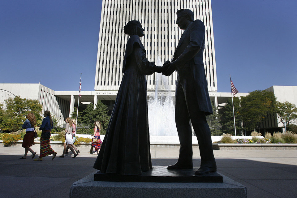 FILE - In this Saturday, Oct. 6, 2012 file photo, women walk by a statue of Joseph and Emma Smith outside the church office building during the 182nd Semiannual General Conference for The Church of Jesus Christ of Latter-day Saints in Salt Lake City. The Church of Jesus Christ of Latter-day Saints has entered a new era after Mitt Romney's run for president in 2012. His candidacy illuminated a changing landscape for the religion, where Americans are growing more curious than fearful about the faith, and allies can be found even among Christians with deep misgivings about Mormon beliefs. (AP Photo/The Salt Lake Tribune, Scott Sommerdorf)