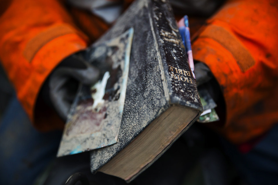 Photo - Elaine Young holds a Bible that she pulled out of the debris field caused by a massive mudslide on Saturday, above the North Fork of the Stillaguamish River onto Highway 530, as recovery efforts continue near Oso, Wash., on Tuesday, March 25, 2014. A scientist working for the government had warned 15 years ago about the potential for a catastrophic landslide in the community where the collapse of a rain-soaked hillside over the weekend killed at least 14 people and left scores missing. (AP Photo/The Seattle Times, Marcus Yam) SEATTLE OUT; USA TODAY OUT; MAGS OUT; TELEVISION OUT; NO SALES; MANDATORY CREDIT TO BOTH THE SEATTLE TIMES AND THE PHOTOGRAPHER