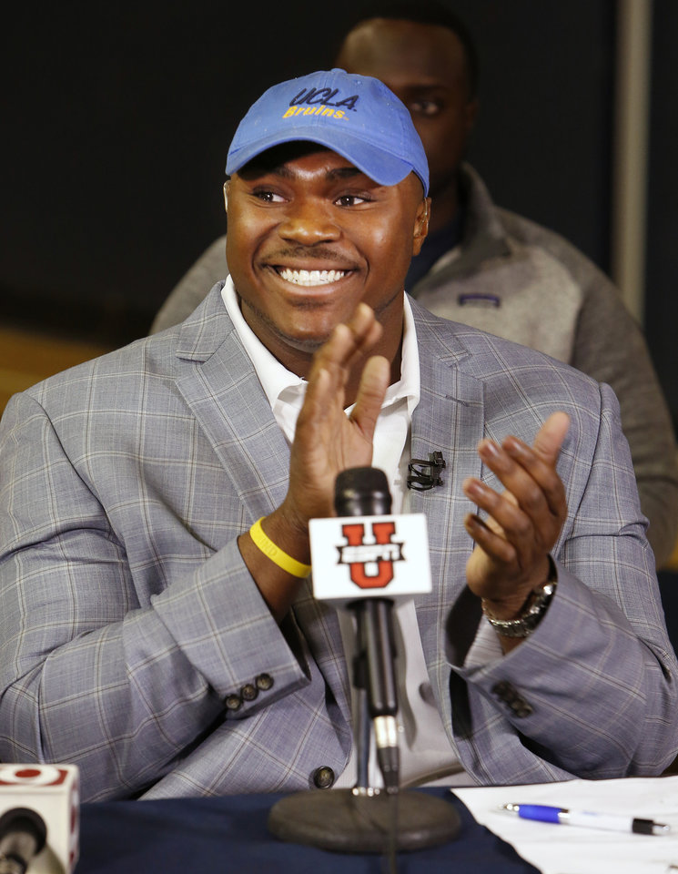 Photo - Casady High School football athlete Josh Wariboko-Alali puts on a UCLA hat during signing day ceremonies at Casady High School in Oklahoma City Wednesday, Feb. 4, 2015. Photo by Paul B. Southerland, The Oklahoman
