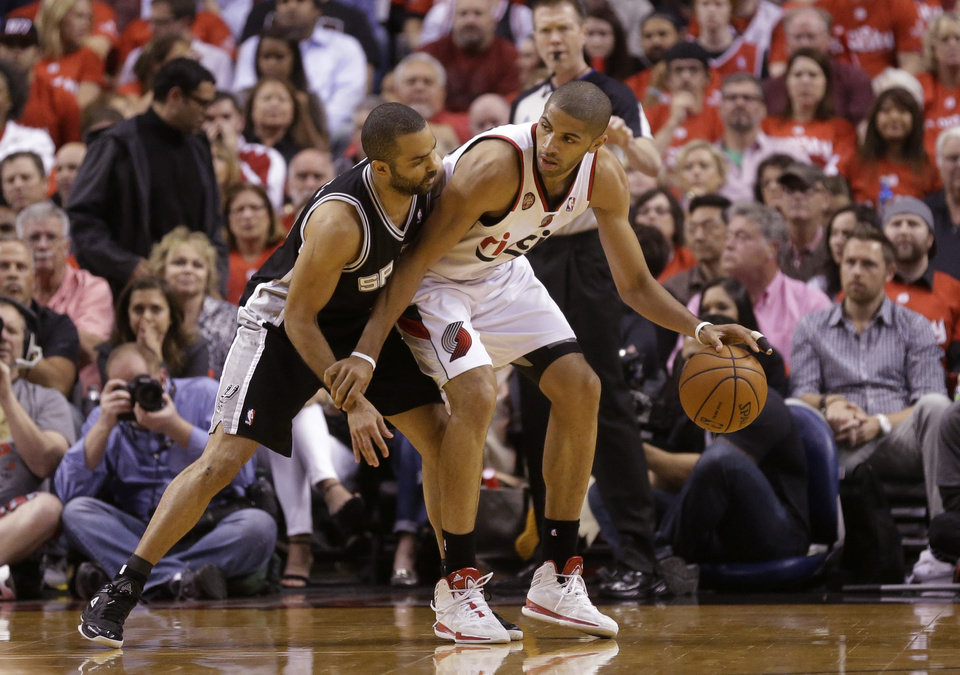 Photo - San Antonio Spurs' Tony Parker, left, guards Portland Trail Blazers' Nicolas Batum, right, in the first quarter during Game 4 of a Western Conference semifinal NBA basketball playoff series Monday, May 12, 2014, in Portland, Ore. (AP Photo/Rick Bowmer)