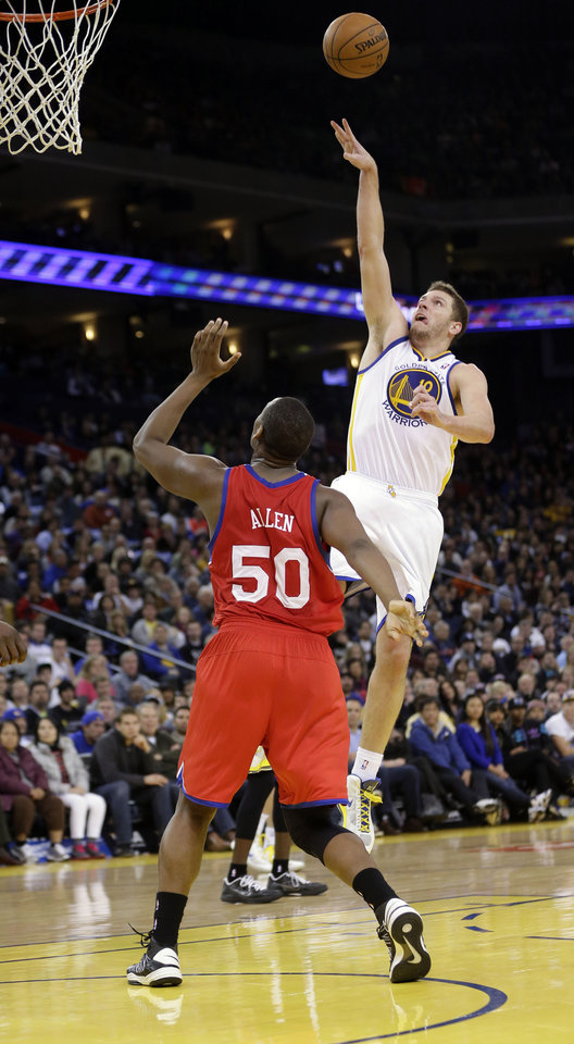 Photo - Golden State Warriors' David Lee (10) shoots to score over Philadelphia 76ers' Lavoy Allen (50) during the second half of an NBA basketball game in Oakland, Calif., Friday, Dec. 28, 2012. Golden State won 96-89. (AP Photo/Marcio Jose Sanchez)