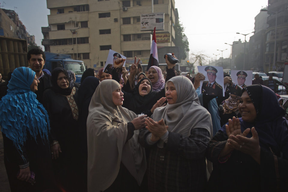 Photo - Egyptians chant slogans while holding pictures of Egypt's Defense Minister, Gen. Abdel-Fattah el-Sissi as they gather near the Imbaba courthouse after an early morning explosion damaged the building, in Cairo, Egypt, Tuesday, Jan. 14, 2014. The courthouse was not a polling station and no one was reported injured in the blast.  Egyptians have started voting on a draft for their country's new constitution that represents a key milestone in a military-backed roadmap put in place after President Mohammed Morsi was overthrown in a popularly backed coup last July. (AP Photo/Khalil Hamra)