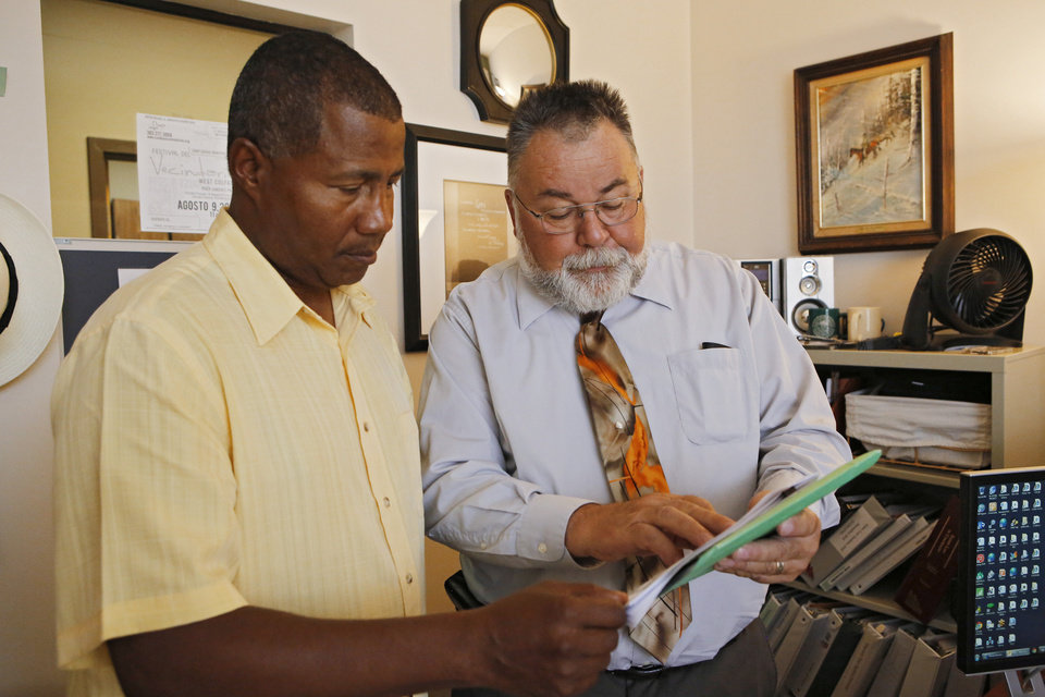 Photo -  William Kistler, right, goes over a clients' information with support specialist Ronald Smith at Kistler's office in Denver.  AP Photo   Ed Andrieski -  AP