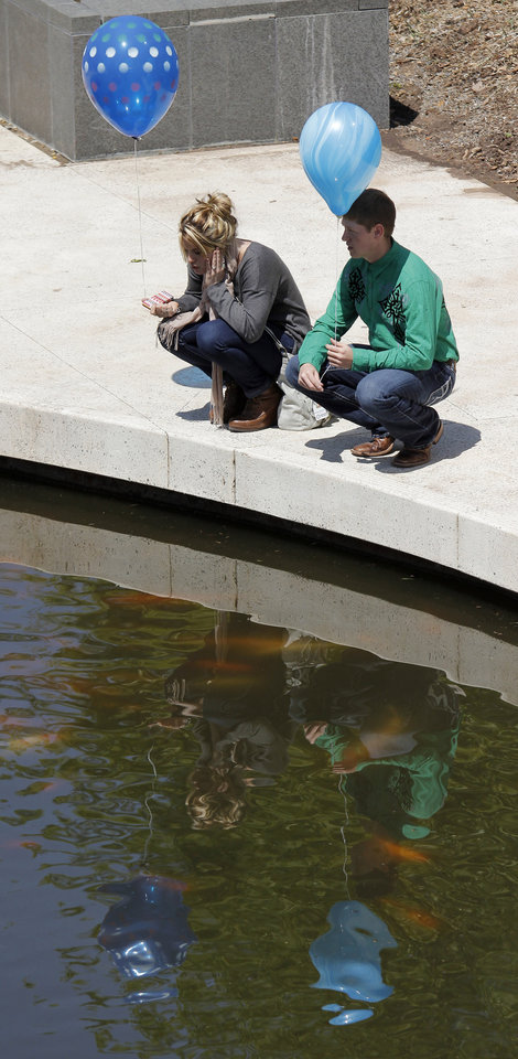A couple pause to watch the Koi fish in the pond at the Myriad Gardens at the Festival of the Arts in downtown Oklahoma City  Wednesday, April 24, 2013. The Hunters are from Piedmont. Photo by Doug Hoke, The Oklahoman