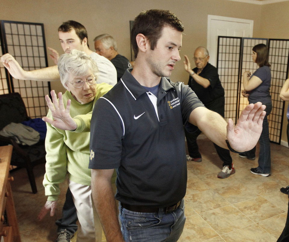 Photo - Instructor Andrew Wright shows student Carol Payne the correct movements during a tai chi class for seniors at the Ntouch Medical Massage and Spa in Edmond. Photo By Paul Hellstern, The Oklahoman