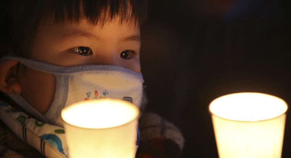 Photo - A child holds candles with a mother during a prayer for people believed to have been trapped in the sunken ferry Sewol, in Ansan, South Korea, Monday, April 21, 2014. South Korean President Park Geun-hye said Monday that the captain and some crew members of the sunken ferry committed
