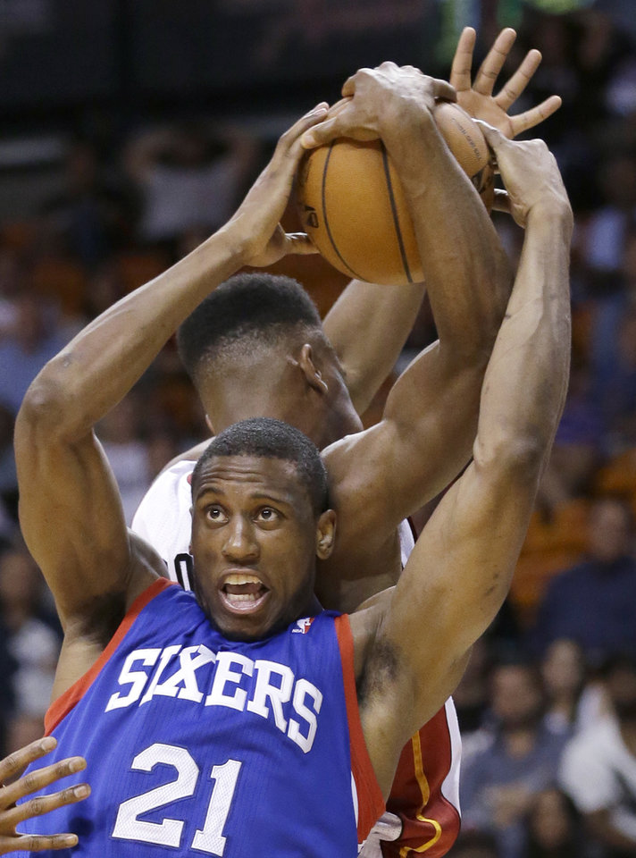 Photo - Philadelphia 76ers forward Thaddeus Young (21) and Miami Heat guard Norris Cole, rear, battle for the ball during the second half of an NBA basketball game on Wednesday, April 16, 2014, in Miami. The 76ers defeated the Heat 100-87. (AP Photo/Wilfredo Lee)