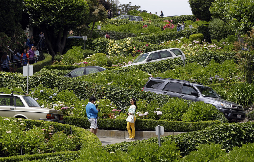 Photo - Motorists make their way down Lombard Street on Tuesday, May 20, 2014, in San Francisco.  San Francisco's crooked street could soon be closed to tourists in the summertime. A transportation commission is scheduled to consider an experimental shutdown of the famously curvaceous block of Lombard Street plus an adjoining block where cars line up and wait.(AP Photo/Marcio Jose Sanchez)
