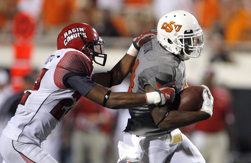 Louisiana-Lafayette\'s Melvin White tries to bring down Oklahoma State\'s Justin Horton in the second half of their game Saturday. Photo by Sarah Phipps, The Oklahoman