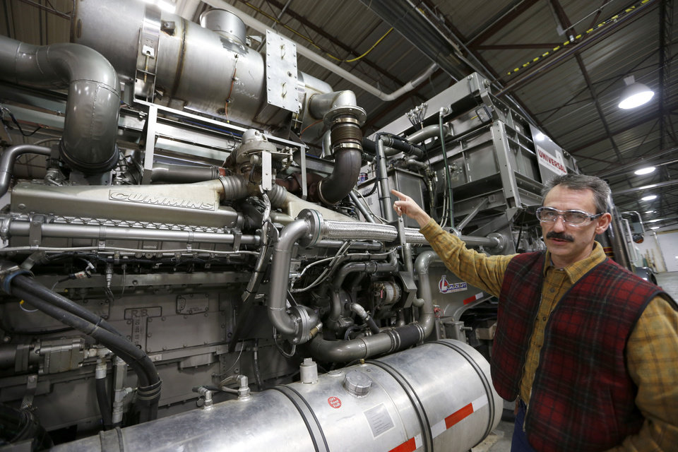 In this photo made on Thursday, Jan. 17, 2013, Universal Well Services fracturing engineering team leader Mike Michaelson points to the 50 litre, 16 cylinder, Cummins diesel engine with four turbo-chargers that has been converted to run on a blend of diesel and natural gas at the Cummins Bridgeway facility in Gibsonia, Pa. Oil- and gas-field companies from Pennsylvania to Texas are experimenting with converting the huge diesel engines that operate pumps that propel millions of gallons of water, sand and chemicals down a well bore in the fracturing process to break apart rock or tight sands that trap natural gas. (AP Photo/Keith Srakocic)