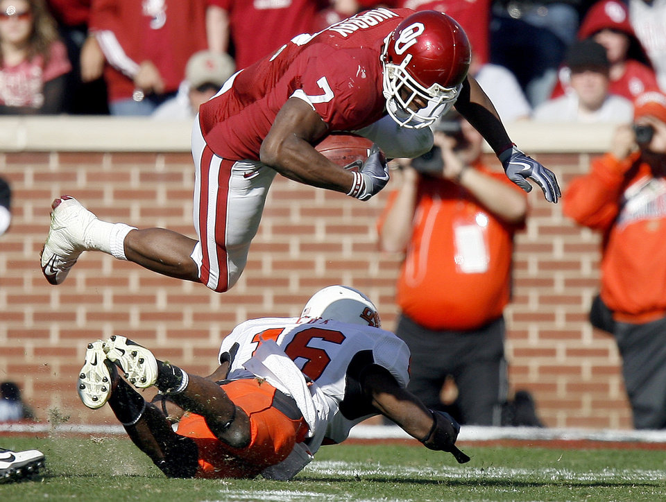 Photo - OU's DeMarco Murray (7) leaps over OSU's Perrish Cox (16) during the first half of the Bedlam college football game between the University of Oklahoma Sooners (OU) and the Oklahoma State University Cowboys (OSU) at the Gaylord Family-Oklahoma Memorial Stadium on Saturday, Nov. 28, 2009, in Norman, Okla. Photo by Sarah Phipps, The Oklahoman