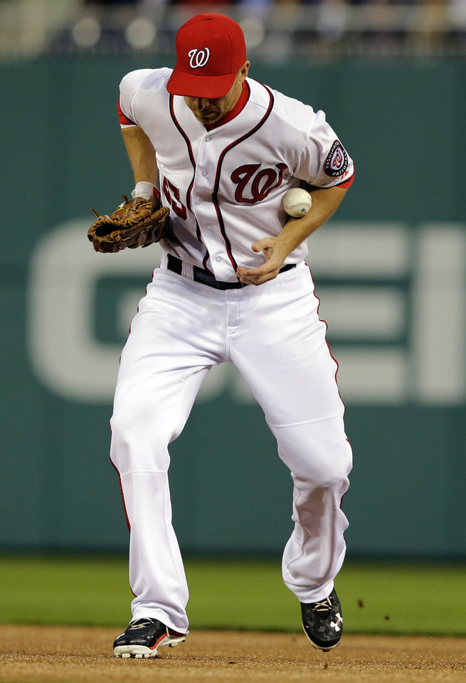 Photo - Washington Nationals first baseman Adam LaRoche (25) cannot handle a ball hit by Detroit Tigers' Torii Hunter during the first inning of a baseball game at Nationals Park, Wednesday, May 8, 2013, in Washington. Hunter was safe at first and LaRoche received an error on the play. (AP Photo/Alex Brandon)
