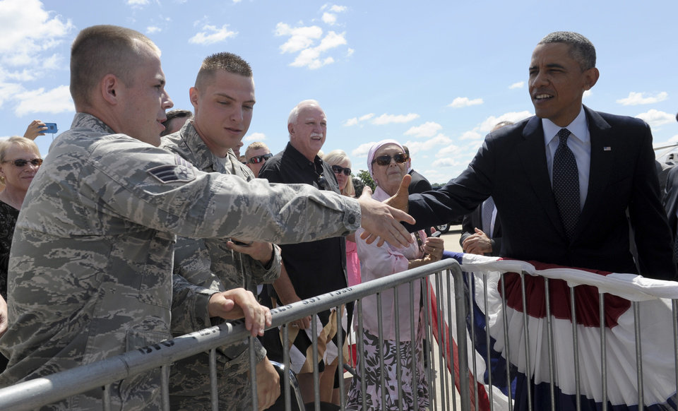 President Barack Obama greets people after on the tarmac arriving at Quad Cities International Airport in Moline, Ill.,Wednesday, July 24, 2013. Obama is traveling to Knox College in Galesburg, Ill., to kick off a series of speeches that will lay out his vision for rebuilding the economy. (AP Photo/Susan Walsh)