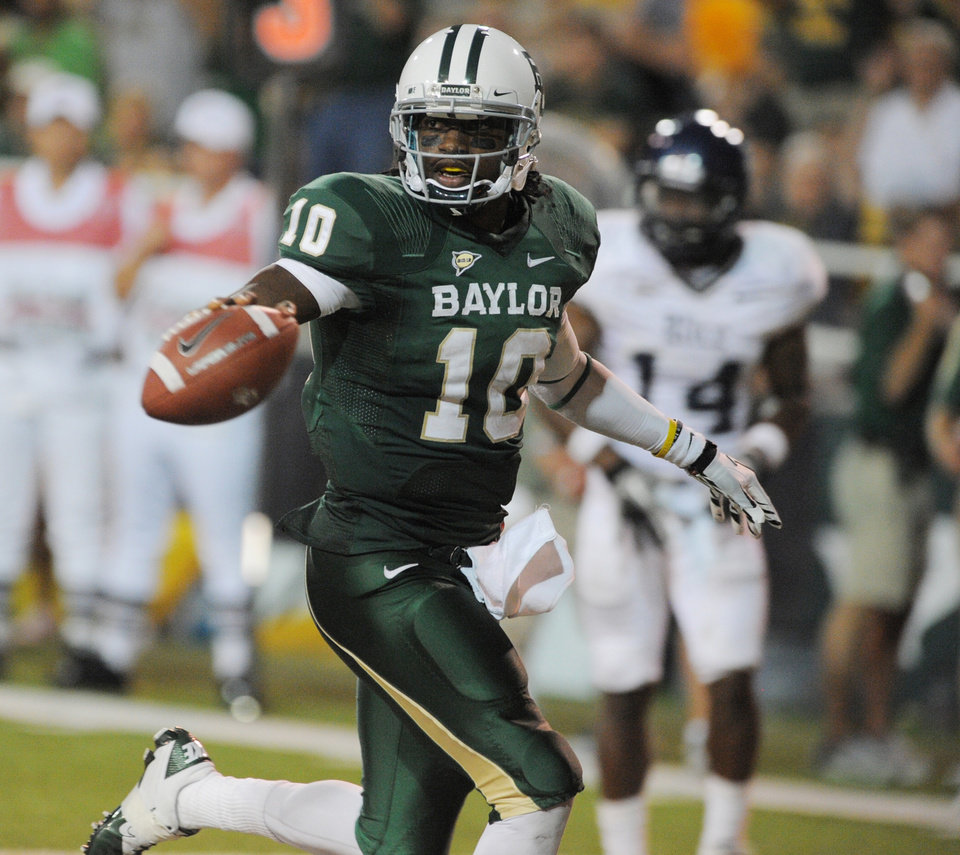 Baylor quarterback Robert Griffin III runs past Rice's Xavier Webb for a third quarter touchdown of an NCAA college football game on Saturday, Sept. 24, 2011, in Waco, Texas.  Baylor won 56-31.(AP Photo/Rod Aydelotte) ORG XMIT: TXRA113