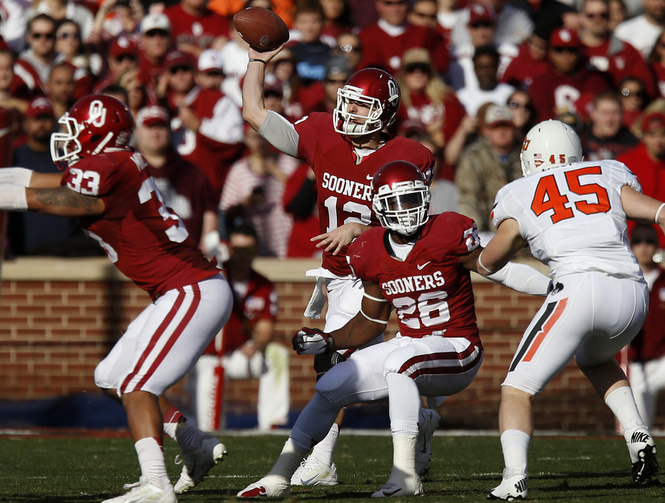 Photo - Oklahoma's Landry Jones (12) throws a pass during the Bedlam college football game between the University of Oklahoma Sooners (OU) and the Oklahoma State University Cowboys (OSU) at Gaylord Family-Oklahoma Memorial Stadium in Norman, Okla., Saturday, Nov. 24, 2012. Oklahoma won 51-48. Photo by Bryan Terry, The Oklahoman