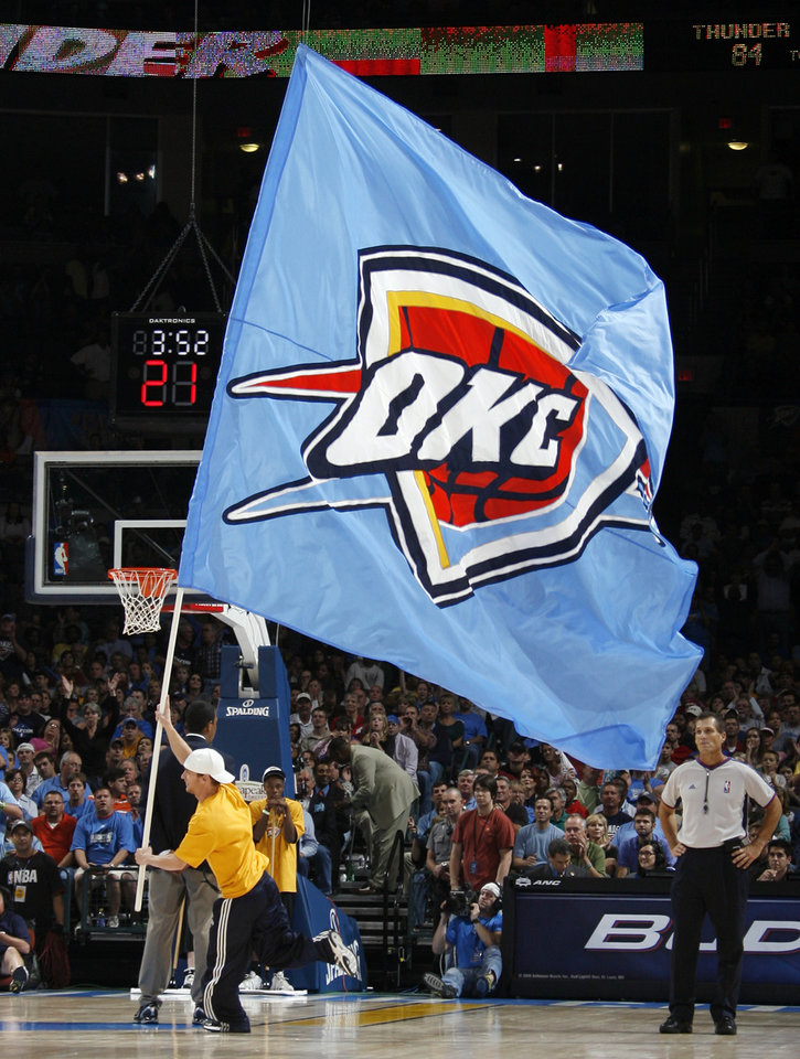 Photo - FIRST REGULAR SEASON WIN: The Oklahoma City team flag makes its way across the court in the fourth quarter during the NBA basketball game between the Oklahoma City Thunder and the Minnesota Timberwolves at the Ford Center in Oklahoma City, Sunday, Nov. 2, 2008. The Thunder won, 88-85. BY NATE BILLINGS, THE OKLAHOMAN  ORG XMIT: KOD