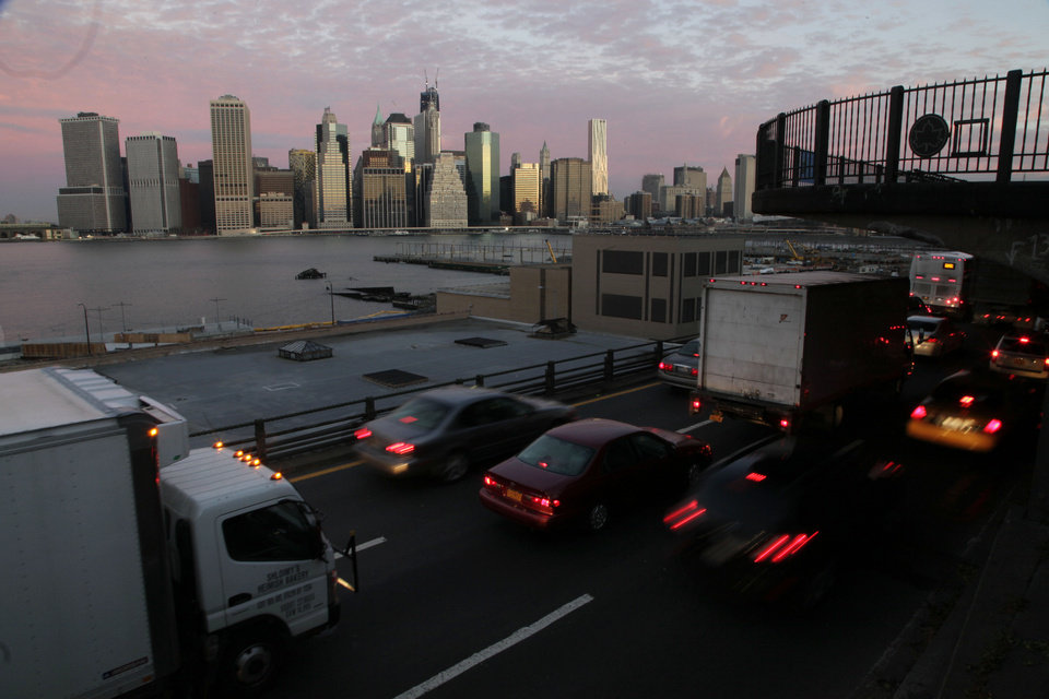 Photo - Early morning traffic in Brooklyn moves slowly beneath the Manhattan skyline, Thursday, Nov. 1, 2012 in New York. New York City moved closer to resuming its frenetic pace by getting back its vital subways Thursday, three days after a superstorm, but neighboring New Jersey was stunned by miles of coastal devastation and the news of thousands of people in one city still stranded by increasingly fetid flood waters. (AP Photo/Mark Lennihan) ORG XMIT: NYML105